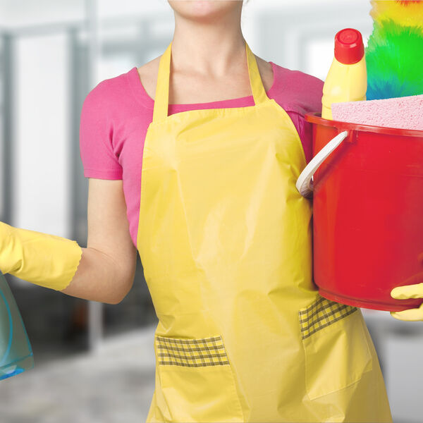 Woman in a yellow  apron and gloves with a bucket full of cleaning supplies