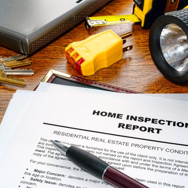 Home inspection report with a pen on top and surrounded by some tools