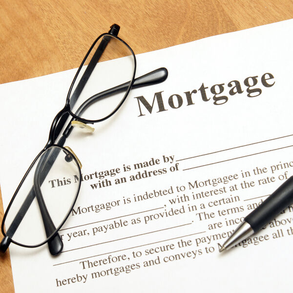 Mortgage contract with a black and silver pen and a pair of black glasses on top