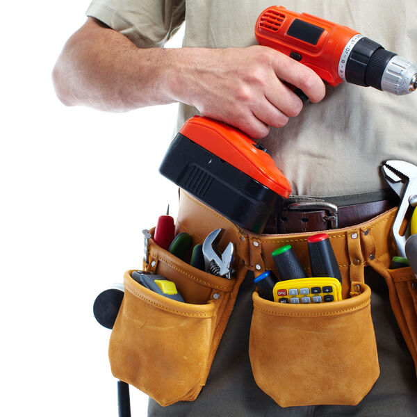 Handyman with tool belt filled with tools and a power drill in one hand